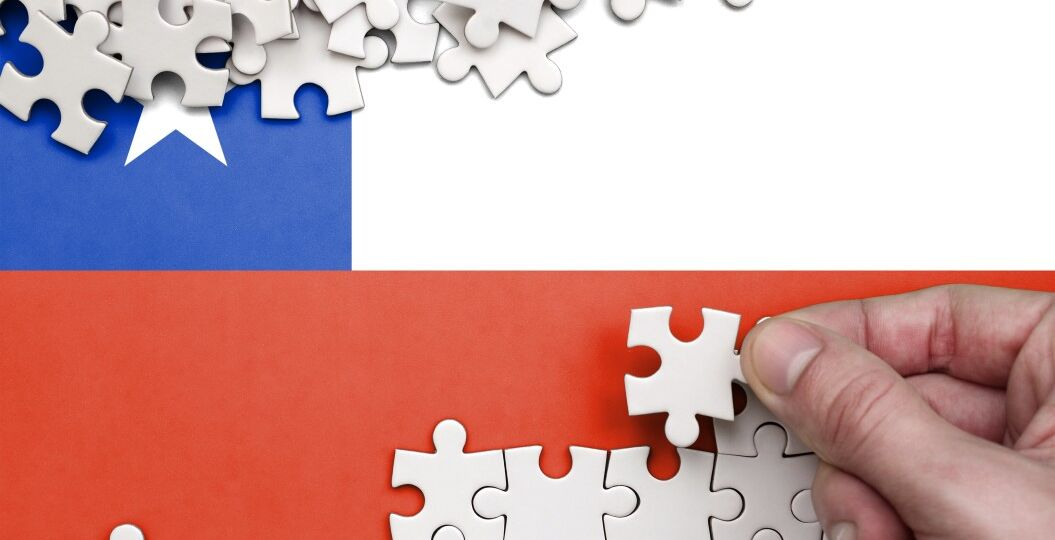chile-flag-is-depicted-on-a-table-on-which-the-human-hand-folds-a-puzzle-of-white-color_t20_ax3eKp