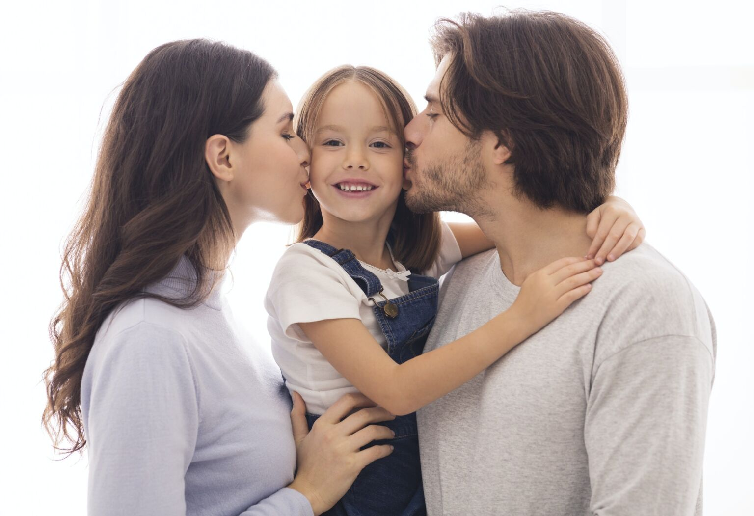 Portrait Of Happy Young Parents Kissing Cheeks Of Their Little Daughter