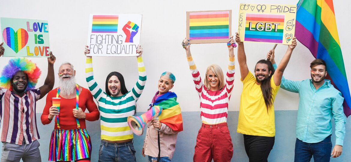Gay people having fun at pride parade with LGBT flags and banners outdoors