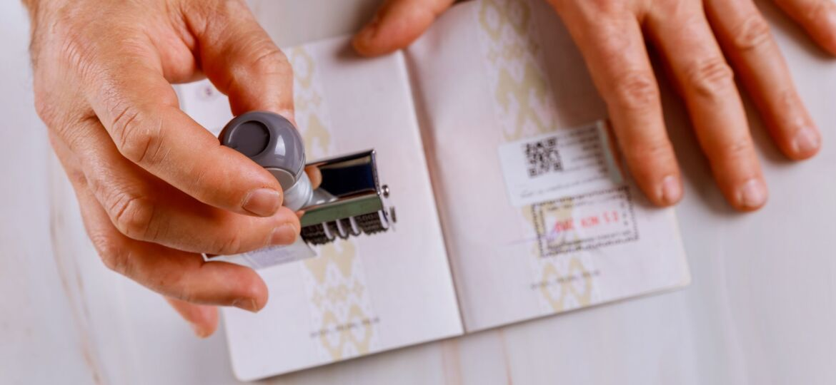 Immigration Service control border control officer puts a stamp in the passport page of passport stamps